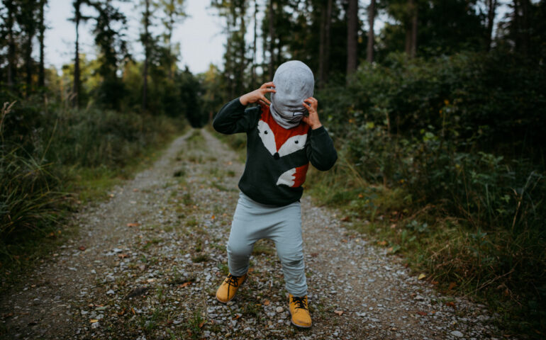 Scary kid with a mask in dark woods
